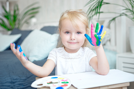 Portrait of little girl playing with paints. Stock Photo