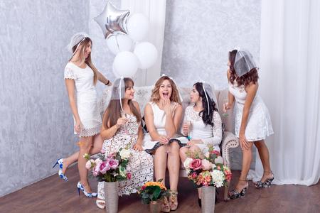 Grupo de cinco amigos elegantes felices de las mujeres jovenes que celebran junto tostando con las flautas del champán mientras que ríen junto que se coloca en una línea en una imagen temática blanca.