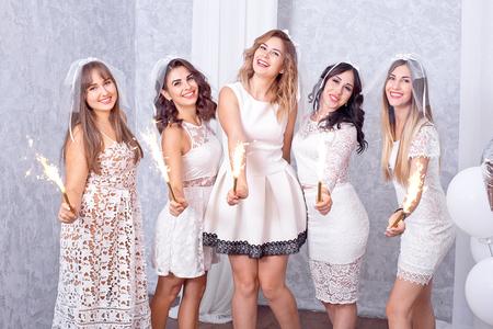 Cinco mujeres jóvenes con estilo felices en elegantes vestidos blancos de pie en una fila riendo y animando mientras celebran con bengalas en el interior