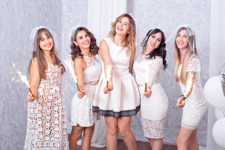 Five happy stylish young women in chic white dresses standing in a row laughing and cheering while celebrating with sparklers indoors