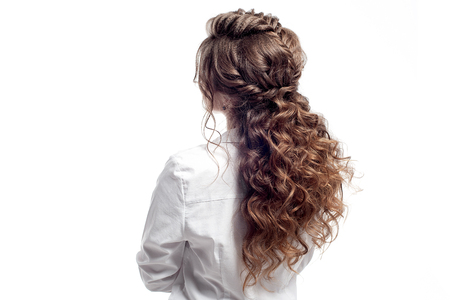 Rear view of female hairstyle. Long brown wavy hair against white background.