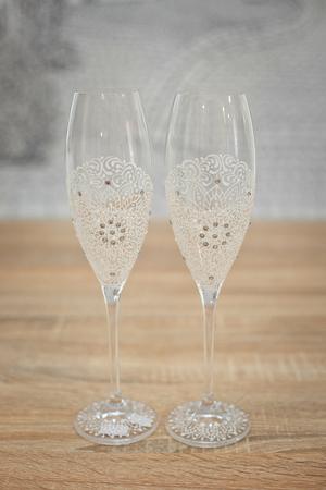 Wedding glasses decorated with cord, beautiful decorated wedding glasses, flowers on wedding glasses, handmade wedding glasses. Stock Photo