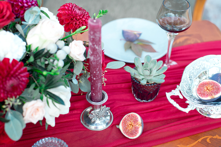 Small succulent alongside a candle on a formal table setting viewed from above on a red tablecloth Stock Photo