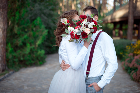 Young happy couple in white shirts having a date outdoor in the forest or park with bouquet of roses.