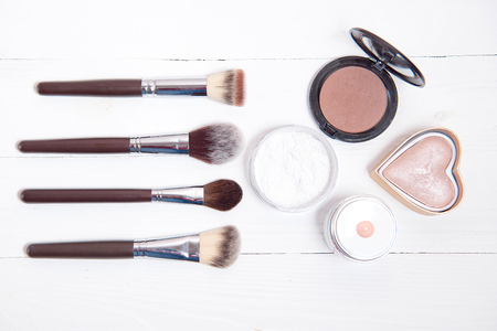 Professional makeup tools on white wooden background.
