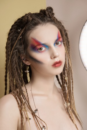 Close-Up Fashion female Model with colorful abstract makeup and dreadlocks hairstyle