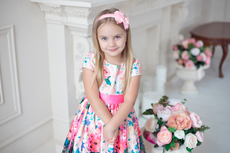 Portrait of little smiling girl child in colorful dress posing indoor Stock Photo