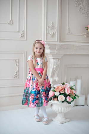 Full-length of little smiling girl child in colorful dress posing indoor