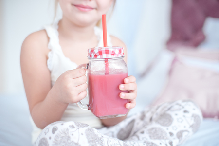 Little girl is drinking fresh red smoothies Stock Photo