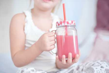 Little girl is drinking fresh smoothies