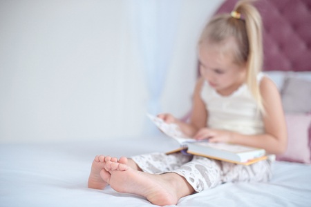Little blonde girl sitting on the bed reading a book Banque d'images