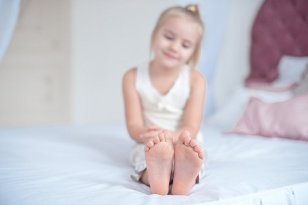 Little blonde girl sitting on the bed Foto de archivo