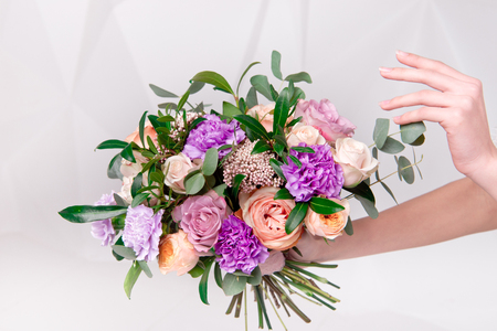 close-up female hands holding bouquet of flowers indoors