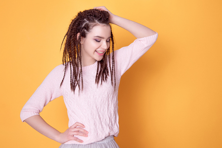 Smiling woman with dreadlocks hairstyle.
