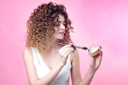 Close-up of a young caucasian woman holding brush and blush palette. Stock Photo