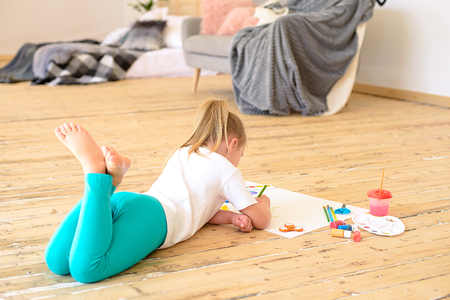 Top view of little blonde girl painting on big white paper while laying on the floor indoors Banque d'images