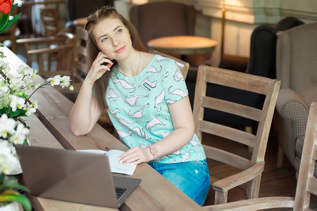 Young caucasian businesswoman in cafe sitting at the table with thoughtful stare.