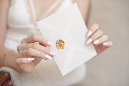 close-up woman with slim body holding invitation envelope card in hands.