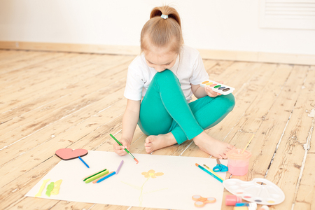 Little blonde girl paints on big white paper sitting on the floor indoors