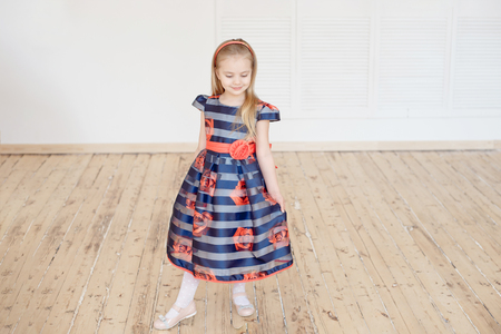 Attractive little girl in colorful dress spinning around indoors Stock Photo