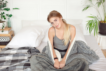 Young happy woman sitting on the bed in the morning wrapped up in white blanket in warm atmosphere