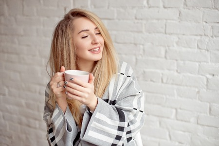 Young happy girl wrapped in a warm blanket looks happy holding cup of tea indoors