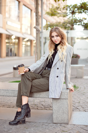 Caucasian fashion woman with cup of coffee sitting near storefront shop windows on the street outdoors Stok Fotoğraf