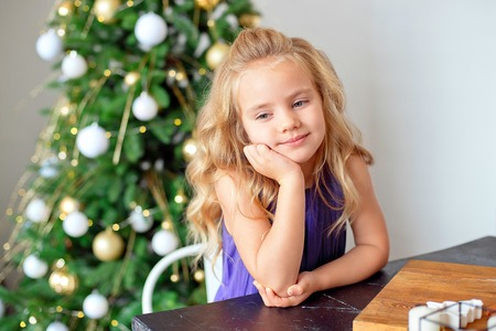 A girl with blond curly hair sits at a table, in the background a Christmas tree, dreams of gifts. Christmas concept, new year Reklamní fotografie
