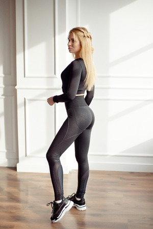 Young slim woman with an athletic body long blonde hair wearing in black sports sportswear top and leggings standing full height in bright yoga room with big panaramic window preparing before training health-life