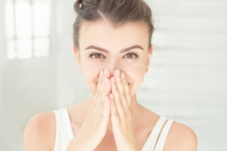 Close-up surprised happy female portrait with brown eyes holding hands on cheeks indoors at white bright room.