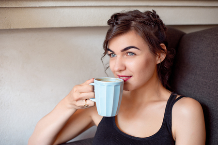Young attractive girl in a black T-shirt and jeans sits in a cafe at the table and drinks coffee in a vintage cup.