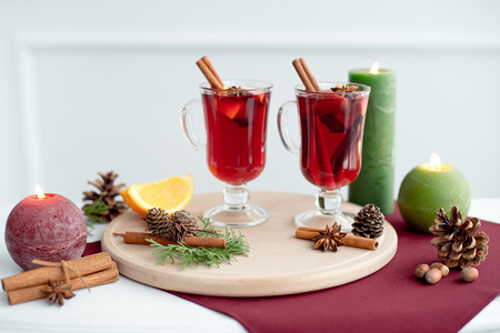 Decorated composition of mulled wine in a glass cup on a white wooden table in a white room.
