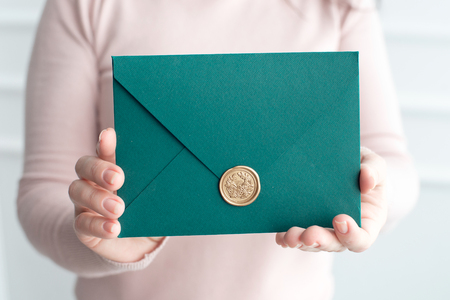 Close-up of woman holding invitation card envelope in hands, front view.