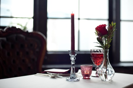 Event table with flower vases, candles in a glass candlestick, towels and wine glasses. Фото со стока