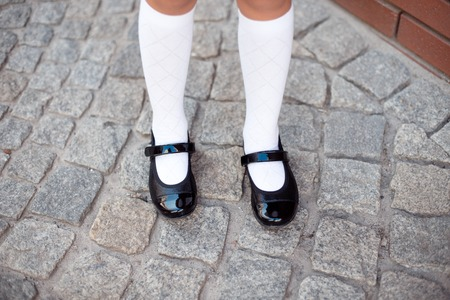 Close-up retro style image of school girls feet in uniform