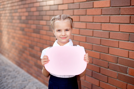 Little girl with blond hair in a white shirt and blue skirt holds an empty board near the upper wall Stok Fotoğraf