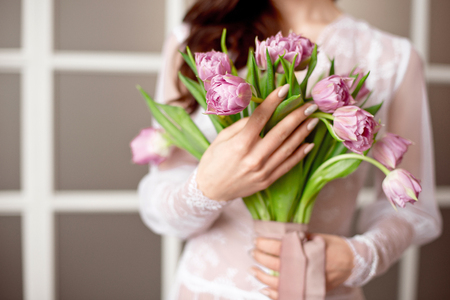 Beautiful young woman in the white dress with flowers tulips in hands on bed at home