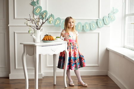 Full length of a little smiling girl in colorful dress posing in a decorated room for the holiday Easter is waiting for an Easter lunch.