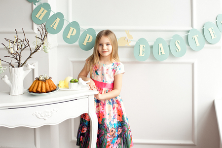 Attractive little girl in a colorful dress posing and smiling against the background of a decorated Easter cake and eggs.