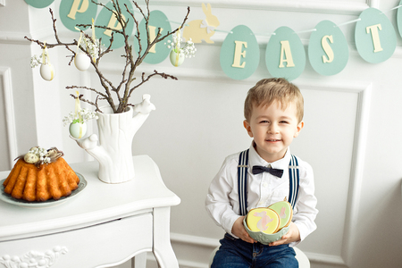 Cute boy in a white shirt and a tassel butterfly sits at a table in a white room on a table Easter decor a vase with branches and Easter eggs gingerbread-shaped rabbits
