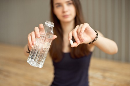 Close-up of a girl is holding a pill with sports additives for training and a bottle of water