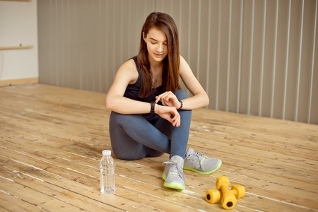 Young girl with dark hair sits on the floor and sets up her fitness tracker to workout in the gym. Stock Photo