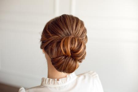 Vue arrière du chignon moyen de coiffure féminine aux cheveux bruns.