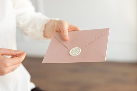 Close-up of woman in white shirt of business style holds in her hand a invitation card, card, letter. Stok Fotoğraf