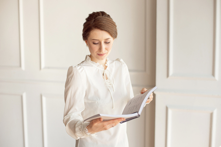 Business woman in a white shirt and black trousers looks documents in hands