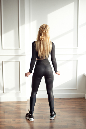 Young slim woman with an athletic body blonde hair wearing in black sports top and leggings standing in bright yoga room with big panoramic window preparing before training health life. 版權商用圖片