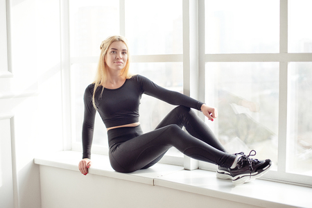 Young slim woman with an athletic body blonde hair wearing in black sports top and leggings standing in bright yoga room with big panoramic window preparing before training health life. Imagens