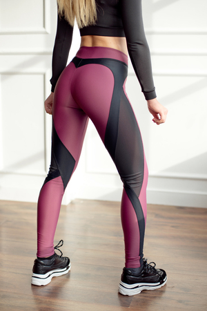 Young slim woman with an athletic body blonde hair wearing in black sports top and leggings standing in bright yoga room with big panoramic window preparing training health life. Imagens