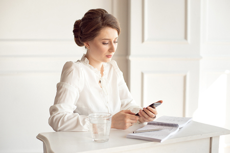 Portrait of a beautiful smiling young brunette businesswoman in a white shirt sitting on a bright modern workstation working with papers . Stock Photo