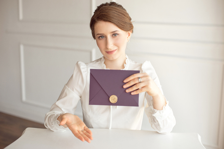 girl in a white business style shirt with a classic hairdo on brunette hair holding a welcome envelope in her hand sitting at a table